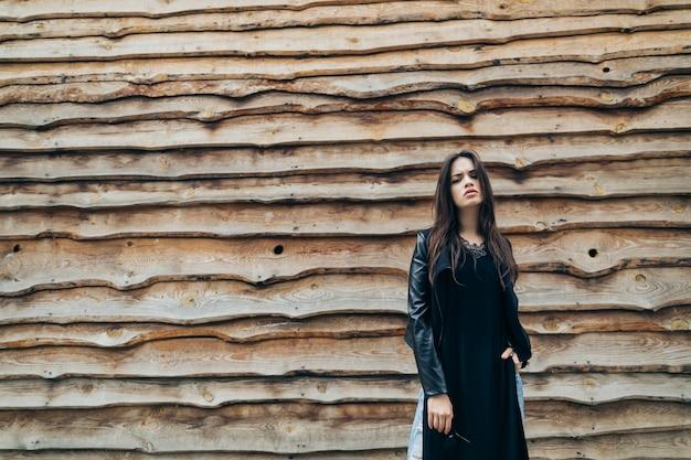 Красивая женщина возле деревянной стены