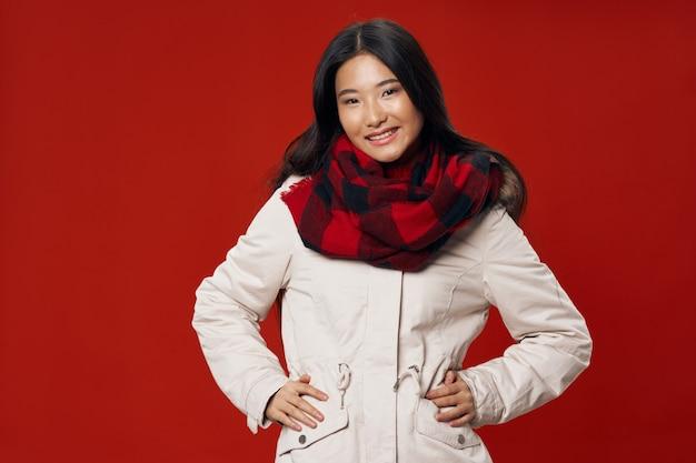 Симпатичная женщина азиатской внешности в теплой куртке и шарфе на шее
