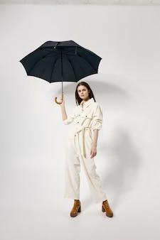 頭上にモダンなファッショナブルなスーツの茶色のブーツ傘のきれいな女性
