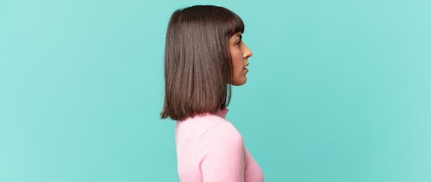 Красивая женщина на виде профиля, желающая скопировать пространство впереди, думает, воображает или мечтает