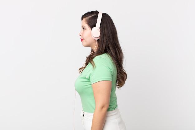 ヘッドフォンで音楽を聴いて、考えたり、想像したり、空想にふけったりするプロフィールビューのきれいな女性
