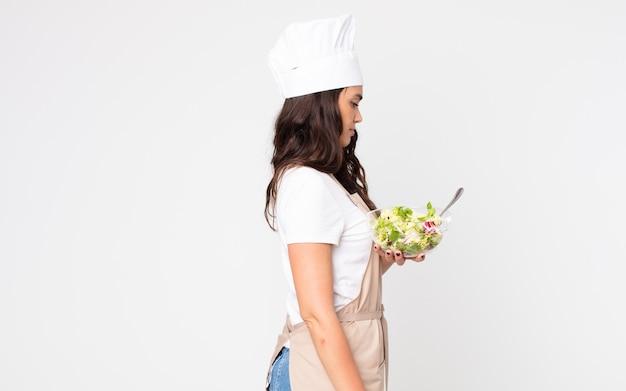 Красивая женщина в профиле думает, воображает или мечтает в фартуке и держит салат