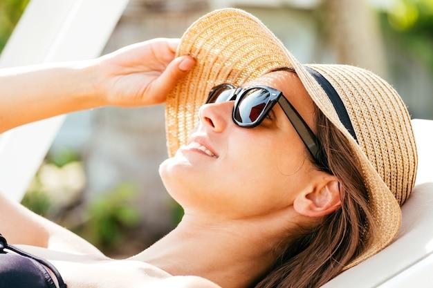 ビーチのきれいな女性。女性のクローズアップの肖像画は麦わら帽子の下で太陽から彼女の顔を隠します
