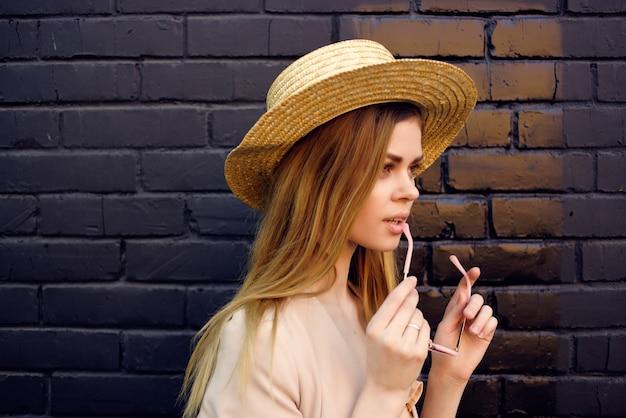 帽子と眼鏡の黒いレンガの壁のモデルを身に着けている通りのきれいな女性。高品質の写真