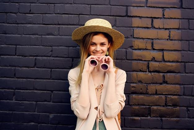 帽子と眼鏡の黒いレンガの壁を身に着けている通りのきれいな女性