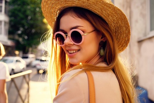 帽子とメガネのライフスタイルを身に着けている通りのきれいな女性
