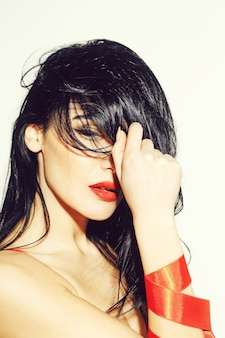 Красивая женщина или милая сексуальная девушка с длинными вьющимися волосами брюнетки, имеет красные губы, макияж на очаровательном лице и бантик на руках, изолированные на белом фоне