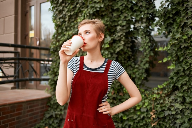 きれいな女性の屋外で一杯のコーヒーレジャー散歩