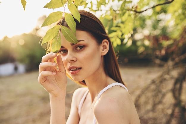きれいな女性の屋外の新鮮な空気の木の葉