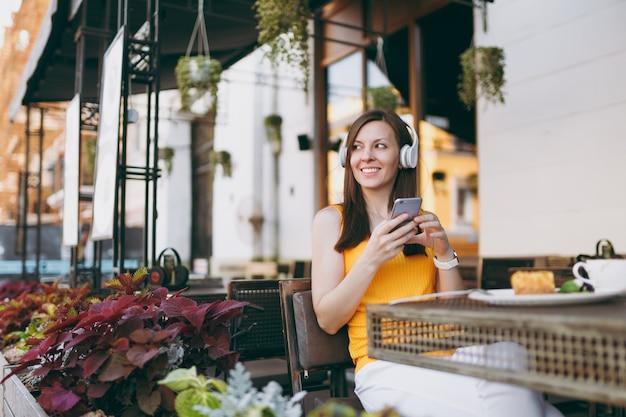 Bella donna in una caffetteria all'aperto di strada seduta al tavolo, ascolta musica in cuffia, usa il telefono cellulare, rilassati al ristorante nel tempo libero