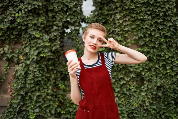 きれいな女性の屋外散歩休暇コーヒーカップ