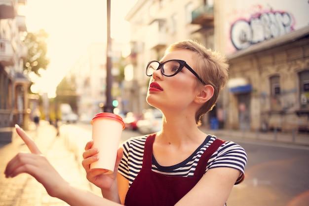 ドリンクウォークとメガネガラスを身に着けている屋外のきれいな女性