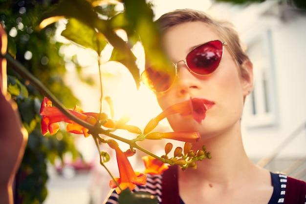 선글라스 꽃 근접 촬영을 입고 야외에서 예쁜 여자