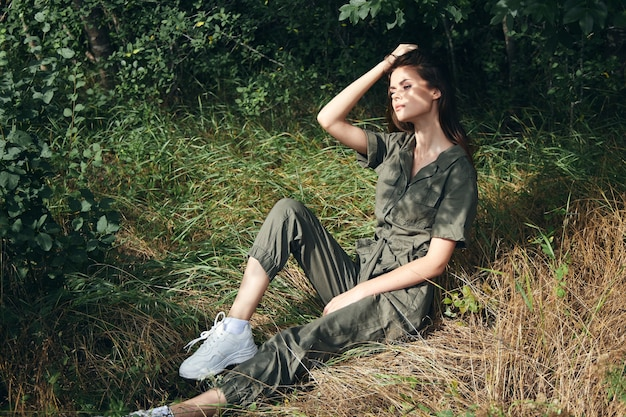 Pretty woman in overalls removes hair from her face and sits on the grass in the forest