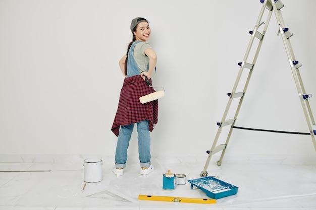 Pretty woman painting walls