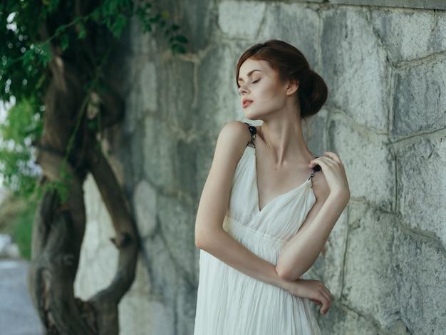 Pretty woman in park near tree stone wall posing mythology