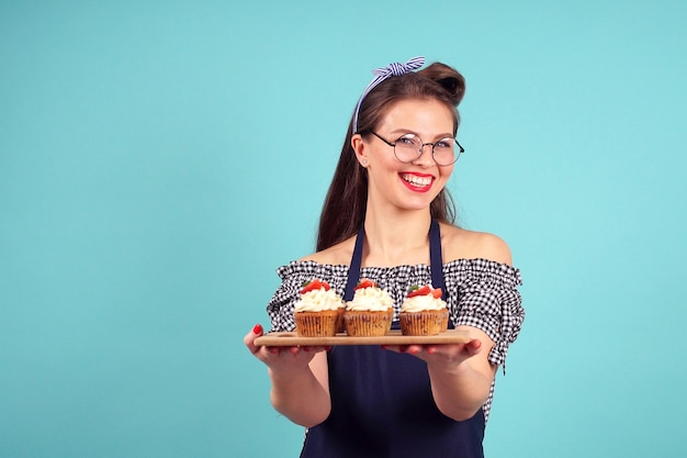 Pretty woman pastry chef with pennies in her hands poses for the camera