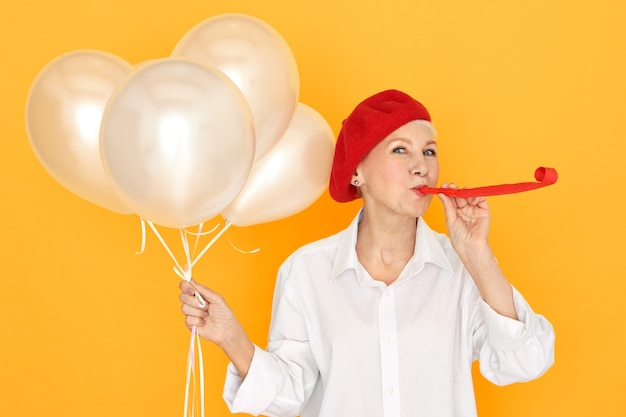 Pretty woman pensioner in red bonnet enjoying party, entertaining her grand children blowing whistle, holding white helium balloons