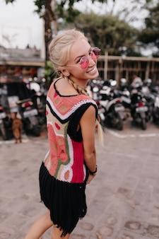 通りで時間を過ごしながら、笑顔でふざけて肩越しに見ているきれいな女性。