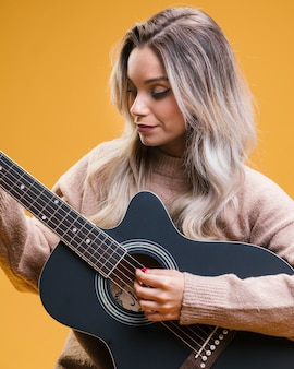 Pretty woman playing guitar against yellow background