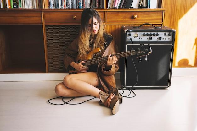 Pretty woman playing guitar near cupboard