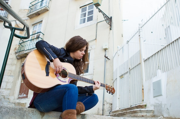 Pretty woman playing guitar on street stairs
