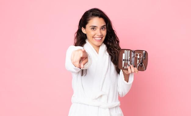 Красивая женщина, указывая на камеру, выбирает вас и держит сумку для макияжа с инструментами для ногтей