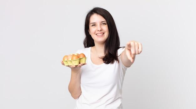 Красивая женщина, указывая на камеру, выбирает вас и держит коробку для яиц