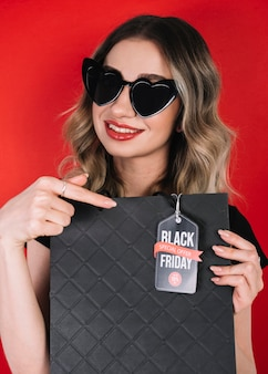 Donna graziosa che indica sulla borsa da venerdì nero