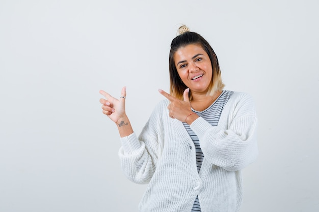 Pretty woman pointing left in t-shirt, cardigan and looking jolly