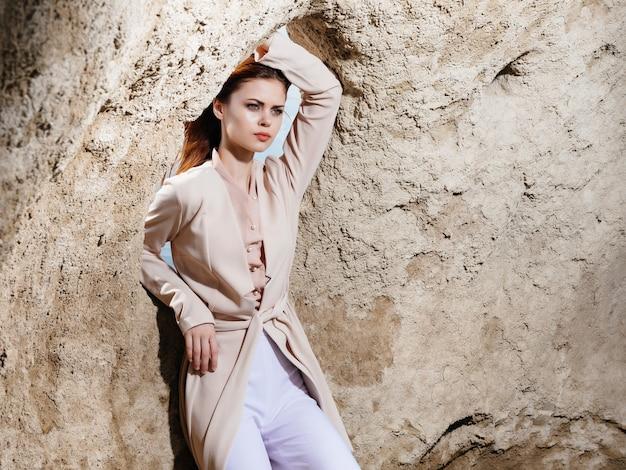 砂の魅力的な外観の岩の近くでポーズをとるきれいな女性