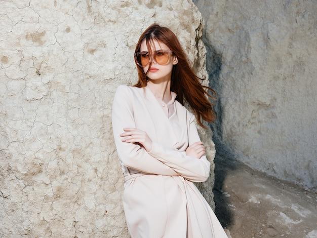 砂のエレガントなスタイルで岩の近くでポーズをとるきれいな女性。高品質の写真