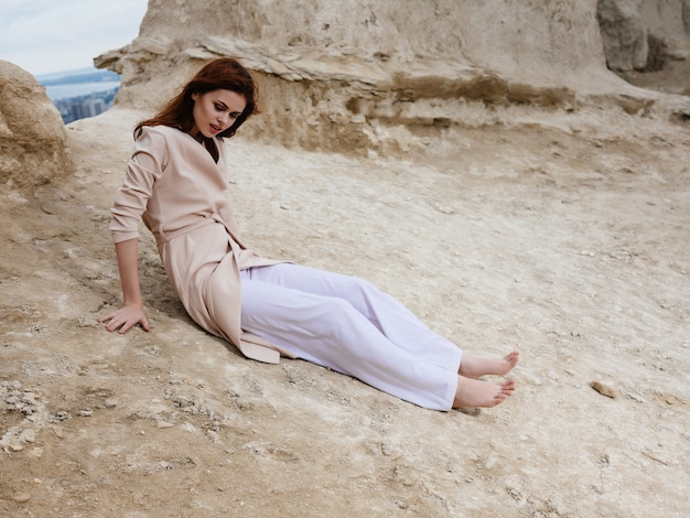 砂のライフスタイルファッションで岩の近くでポーズをとるきれいな女性。高品質の写真