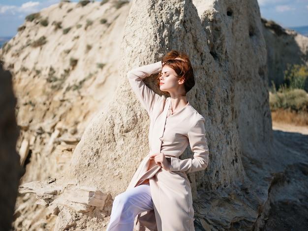 砂のライフスタイルファッションで岩の近くでポーズをとるきれいな女性
