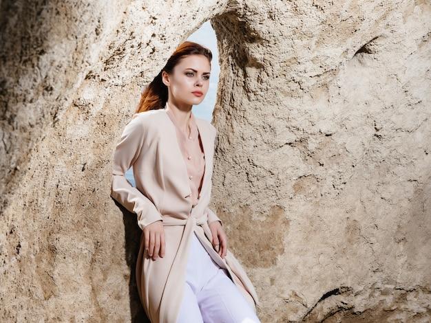 岩のライフスタイルの近くでポーズをとるきれいな女性。高品質の写真