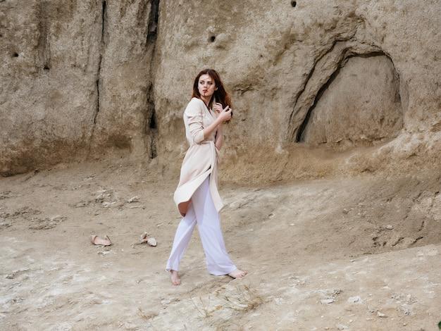 Pretty woman posing near rocks in the sand attractive look