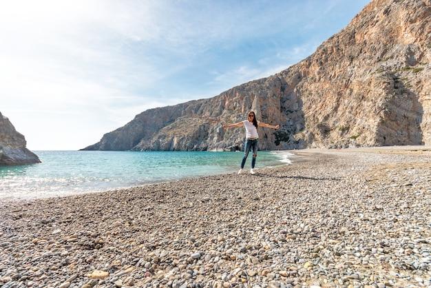 Красивая женщина позирует на пляже с красивой лагуной