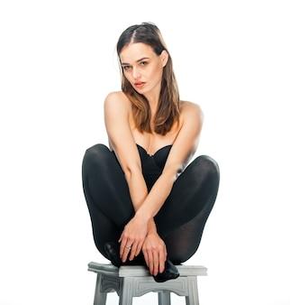 예쁜 여자는 흰색 배경 위에 의자에 검은색 탑과 레깅스에 앉아 포즈를 취합니다. 긴 검은 머리를 가진 여자는 손을 꼬고 다리를 꼬고 앉습니다.
