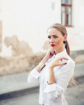 Pretty woman posing in summer on the street. red lips and red nails style