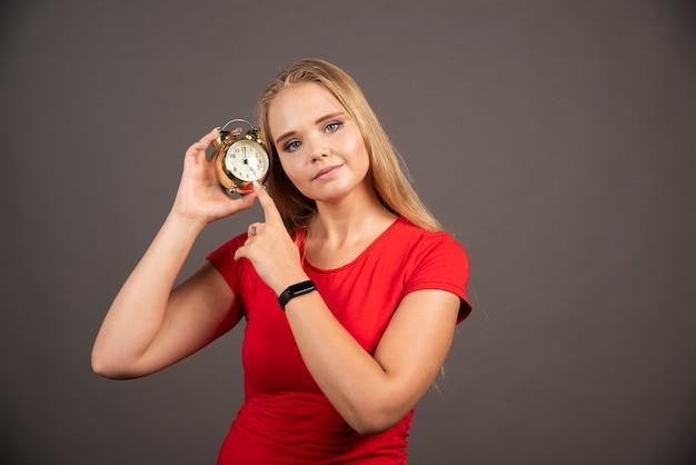 Bella donna in posa con l'orologio sulla parete scura.