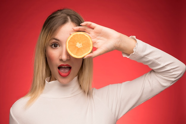 Pretty woman posing with orange slice