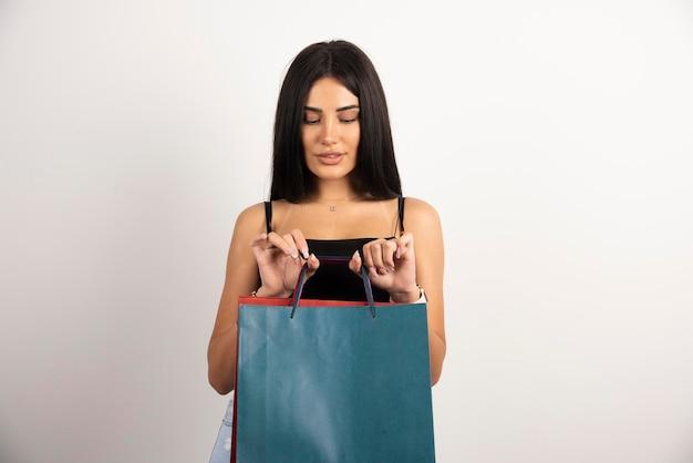 ベージュの背景に買い物袋でポーズをとるきれいな女性。高品質の写真