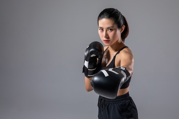 A pretty woman practicing boxing.
