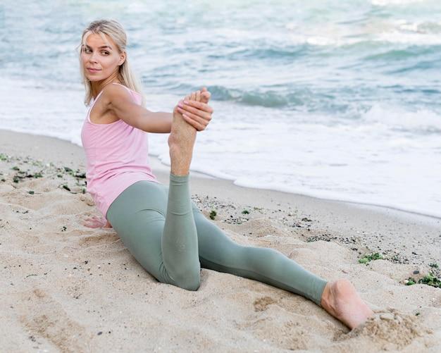 Красивая женщина упражнениями йоги на пляже