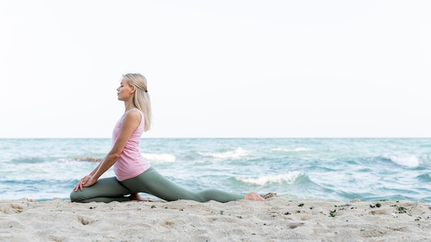 Pretty woman practicing yoga at the beach