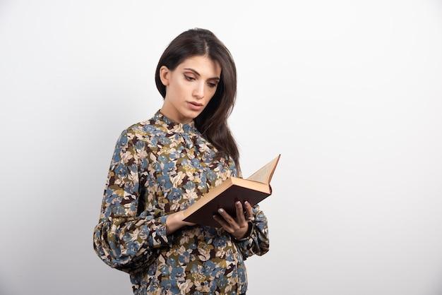 Bella donna che legge un libro con attenzione.