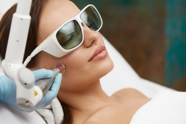보호 안경을 착용하는 레이저로 얼굴 치료를받는 예쁜 여자, 소녀 스파 클리닉에서 성형 절차를 갖는
