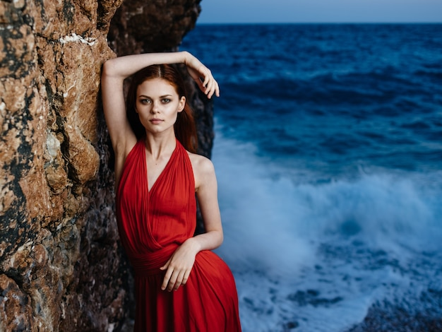 Pretty woman in red dress rocky mountains landscape ocean waves. high quality photo