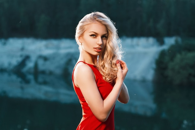 Pretty woman in red dress standing near the mountain