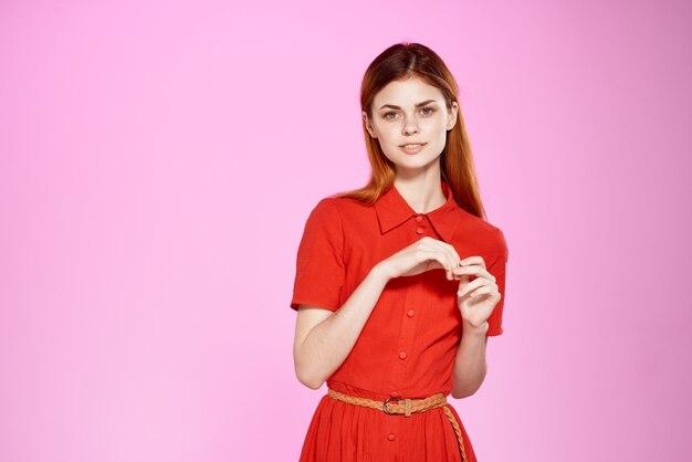 예쁜 여자 빨간 드레스 패션 핑크 배경 포즈. 고품질 사진